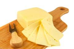 Block des Käses und der Scheiben auf Schneidebrett mit Messer Lizenzfreies Stockfoto
