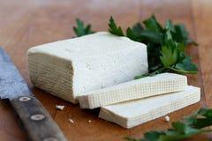 Block des weißen Tofus mit zwei Tofuscheiben, rustikales Messer und frisch Lizenzfreie Stockbilder