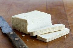 Block des weißen Tofus mit zwei Tofuscheiben und rustikales Messer flehen an an Stockfotografie