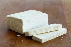 Block des weißen Tofus und zwei Tofuscheiben auf hölzernem hackendem Brett Stockfotos