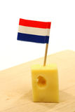 Block of Dutch cheese. With a little Dutch flag toothpick in it to pick it up Royalty Free Stock Photo