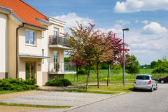 Block of flats in green nature with car parked Stock Photo