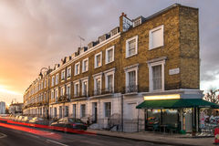 Block of flats in London. Block of sets with a coffee and tea shop in the corner, over sunset and the light of the cars marking lines Royalty Free Stock Image