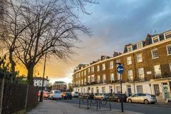 Block of flats in London at sunset. Block of flats at sunset in london and many cars stopped at the red light during the rush hour Royalty Free Stock Images