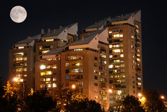 Block of flats by night with full moon above Royalty Free Stock Images