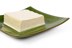 Asian vegetarian food : Block of fresh Tofu on plate isolated on white background Royalty Free Stock Photography