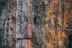 Block of granite with veins of iron ore Stock Photos