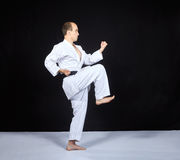 Block by hand and blow leg is training the athlete in karategi Royalty Free Stock Photo