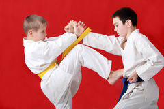 Block hands and blow kicking are performing athlete with yellow belt against an athlete with a blue belt Stock Photos