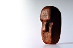 Block Head. Roughly hewn wooden head in the style of the Easter Island statues, shot against a white background with space on the left for text etc royalty free stock images