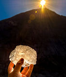 Block of ice in hand. A piece of the briksdal glacier being held up to reflect the sunset. taken at the base of the glacier in Olden,Norway stock photography