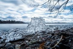 Block of ice on lake on early spring day. A block of ice on the shore of a lake on an early spring day, long exposure Stock Image