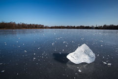 Block of ice lying on the surface of a frozen pond Stock Image