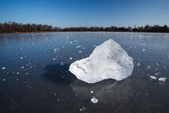 Block of ice lying on the surface of a frozen pond Stock Photos