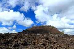 Block Lava and Ash Volcano at Newberry National Monument, Oregon. The cone of an ash volcano is towering above the wide open beds of block lava that make up the Royalty Free Stock Photos