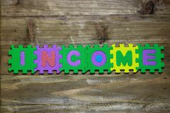 Block letters and word income with wood background Royalty Free Stock Photography