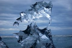 Melting ice in front of a dark cloudy sky royalty free stock image