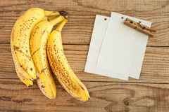 Block note on wooden table next to four bananas Royalty Free Stock Photo