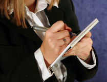 Block notes. Close-up of a woman taking notes on a paper stock images