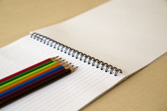 Block notes and pencils. Colorful pencils and block notes on the desk Stock Photos