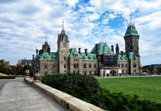 Block of Parliament Hill. Ottawa Canada built in the Victorian High Gothic style standing against the background of the cloudy sky royalty free stock photography