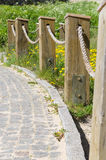 Block pavement footpath and fence rope barrier Stock Photo