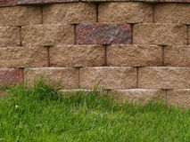 Block Retaining Wall. Green grass alongside multi-colored blocks on a retaining wall Stock Photo