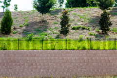 Block Retaining Wall Topped With Black Iron Fence Royalty Free Stock Photos