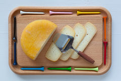 Block of tasty cheese on cutting board with a knife and golf tee Stock Photo