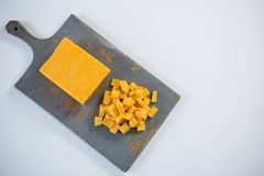 Block und Würfel des Käses auf hackendem Brett Lizenzfreies Stockfoto