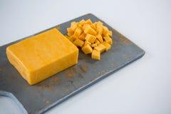 Block und Würfel des Käses auf hackendem Brett Lizenzfreie Stockbilder