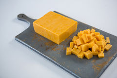 Block und Würfel des Käses auf hackendem Brett Lizenzfreie Stockfotografie