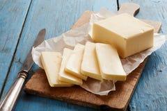 Block von Butter auf hölzernem Schneidebrett Stockbilder