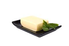 Block von Butter und Minze treiben auf Platte Blätter Lizenzfreie Stockfotografie