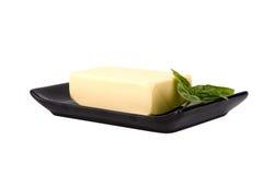 Block von Butter und Minze treiben auf Platte Blätter Stockbild