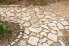 Block von den Steinen, die eine Kreisbahn bilden Kopierte Ziegelsteine, welche die Pflasterung zeichnen Unerwünschte Unkräuter, d Stockfotos