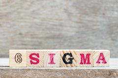 Block in word 6 sigma on wood background royalty free stock photography