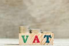 Block in word VAT Value added tax with coin in down trend on wood background. Block in word VAT Abbreviation of Value added tax with coin in down trend on wood royalty free stock photo