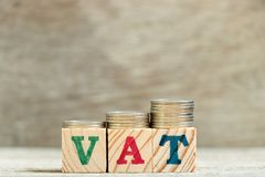 Block in word VAT (Abbreviation of Value added tax) with coin. In up trend on wood background royalty free stock photography