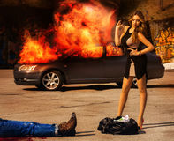 Blockbuster. Girl with posh figure stands over a bag full of mon. Ey EUR amid exploding car. Outdoors Stock Image
