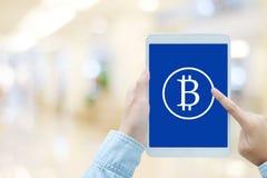 Blockchain概念,在片剂屏幕上的Bitcoin象在手中在b 库存图片
