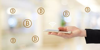Blockchain概念, Gloden在巧妙的电话的bitcoins象在公共汽车上 库存图片