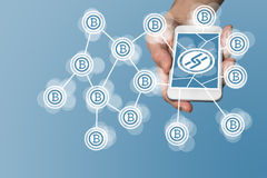 Blockchain and bitcoin concept with hand holding modern smart phone as example for fin tech technology Stock Image