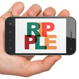 Blockchain concept: Hand Holding Smartphone with Ripple on  display. Blockchain concept: Hand Holding Smartphone with Painted multicolor text Ripple on display Royalty Free Stock Images
