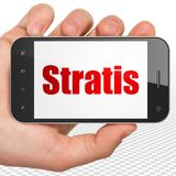 Blockchain concept: Hand Holding Smartphone with Stratis on display. Blockchain concept: Hand Holding Smartphone with red text Stratis on display, 3D rendering Royalty Free Stock Image