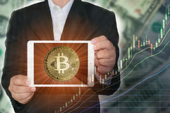 Blockchain concept. Rise of Bitcoin price. Business man holding tablet showing bitcoin on screen with increasing price graph and dollar bills in background Royalty Free Stock Photos