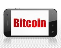 Blockchain concept: Smartphone with Bitcoin on display. Blockchain concept: Smartphone with red text Bitcoin on display, 3D rendering Royalty Free Stock Photos