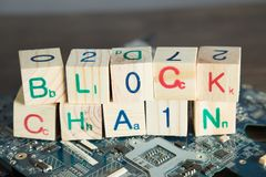 Blockchain concept. Wood blocks say block chain with binary code. On motherboard with wood background royalty free stock images