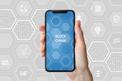 Blockchain and cryptocurrency concept. Hand holding modern bezel-free smartphone in front of neutral background Royalty Free Stock Photos