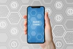 Blockchain and cryptocurrency concept. Hand holding modern bezel-free smartphone in front of neutral background Royalty Free Stock Photography